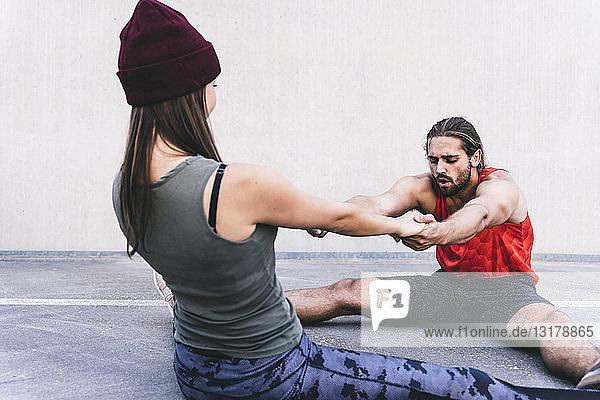 Fit junges Paar bei Partnerübungen