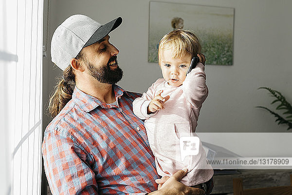 Father holding his little daughter on his arm  playing with his smartphone
