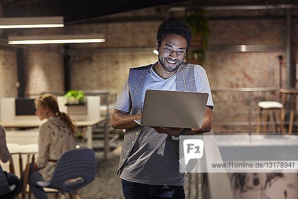 Junger Mann arbeitet in einem kreativen Start-up-Unternehmen und benutzt einen Laptop