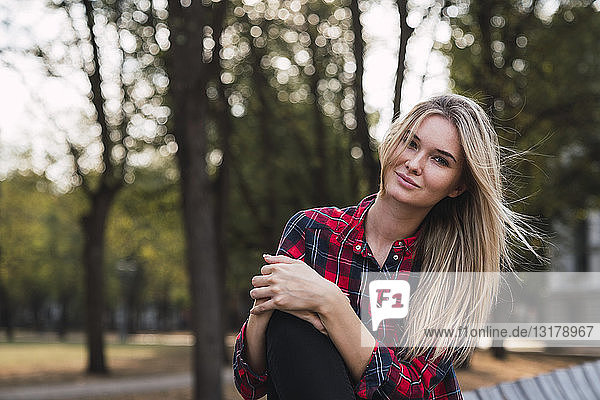 Porträt einer blonden jungen Frau  die im Herbst auf einer Bank sitzt