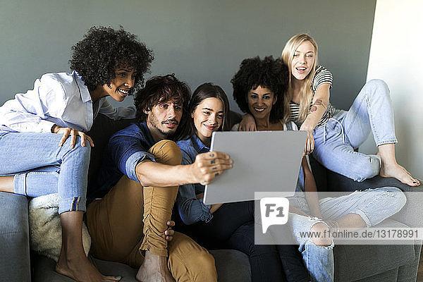 Freunde sitzen auf der Couch und schauen auf die Tafel