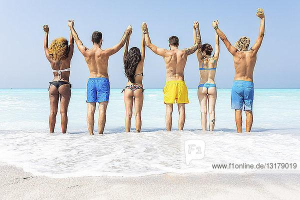 Gruppe von Freunden am Strand  die mit erhobenen Armen im Meer stehen