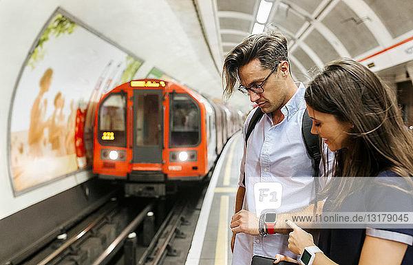 Großbritannien  London  Ehepaar wartet am U-Bahn-Bahnsteig und schaut auf Smartwatch