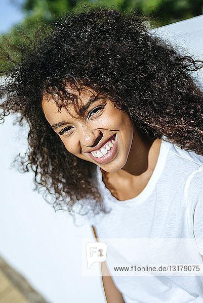 Porträt einer lachenden jungen Frau mit lockigem Haar