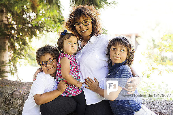 Portrait of smiling mature woman with three children