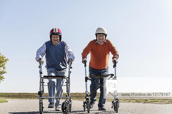 Zwei alte Freunde tragen Schutzhelme und nehmen an einem Laufrad-Rennen teil