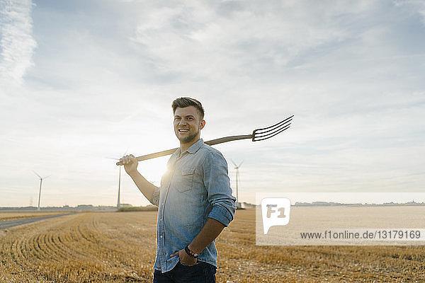 Porträt eines lächelnden jungen Mannes  der eine Mistgabel hält und auf einem Stoppelfeld steht