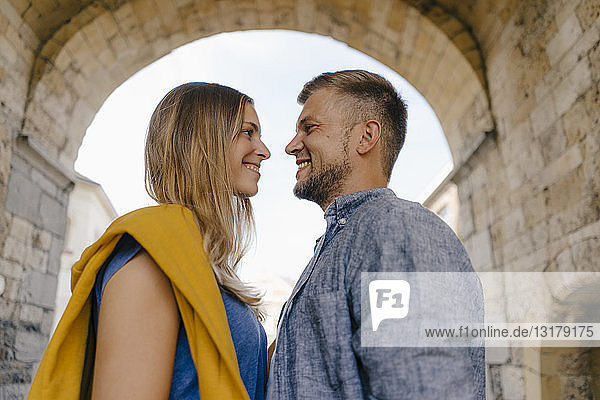 Young couple smiling at each other in the city