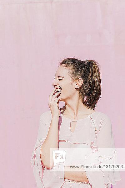 Lachende junge Frau vor rosa Wand