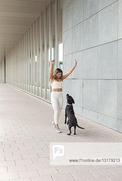 Lächelnde junge Frau in weißer Sportkleidung spielt mit ihrem Hund
