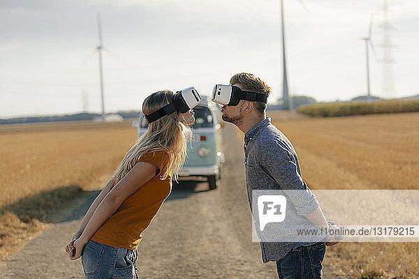 Junges Paar mit VR-Brille küsst sich am Wohnmobil in ländlicher Landschaft