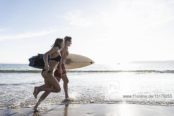 Frankreich  Bretagne  junges Paar mit im Meer laufendem Surfbrett