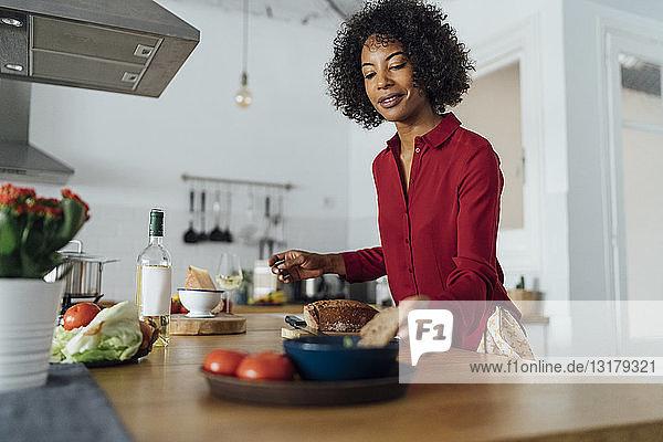 Frau steht in der Küche und schneidet Brot