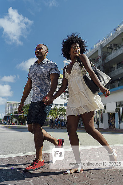 USA  Florida  Miami Beach  happy young couple crossing the street