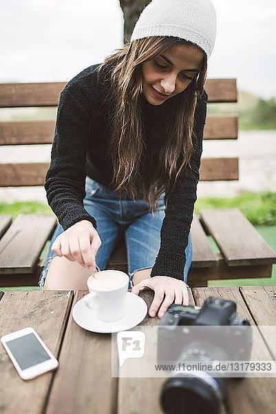 Young photographer sitting on bench outdoors with a cup of coffee
