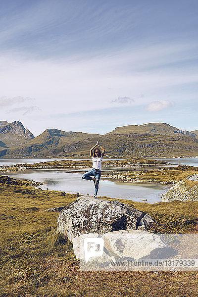 Norwegen  Lofoten  junge Frau steht auf einem Felsen auf einem Bein und macht Yoga