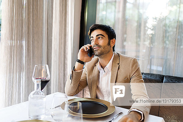Man sitting at table in a restaurant talking on cell phone