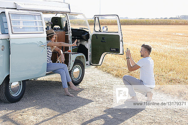 Young man taking cell phone picture of girlfriend inside camper van in rural landscape