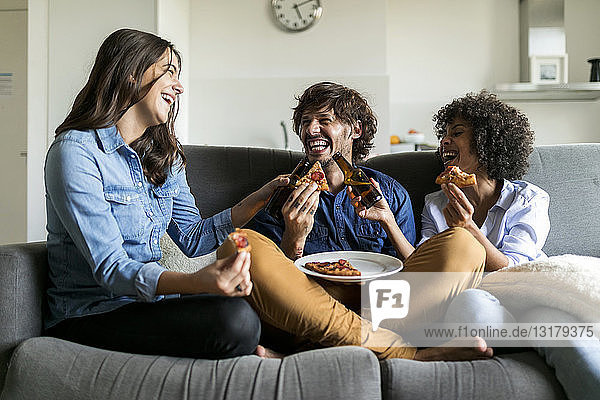 Cheerful friends sitting on couch drinking beer and eating pizza