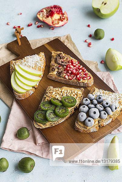 Brotscheiben mit verschiedenen Belägen auf Holzbrett