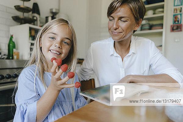 Glückliche Mutter und Tochter sitzen zu Hause am Tisch in der Küche und spielen mit Himbeeren