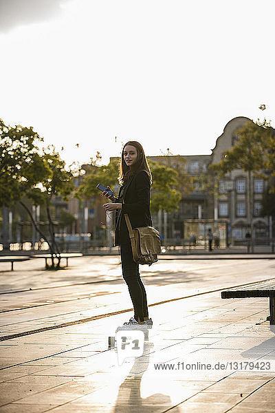 Junge Frau mit Handy auf Longboard in der Stadt