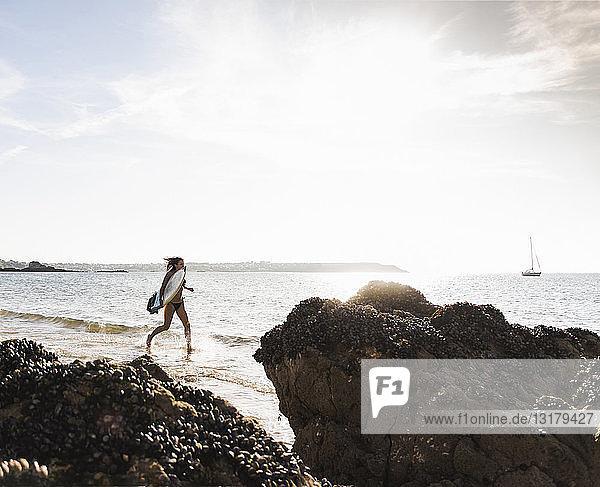 Frankreich  Bretagne  junge Frau mit Surfbrett im Meer