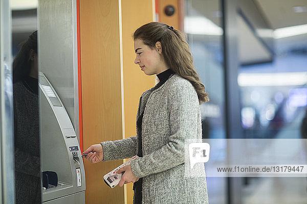 Junge Frau in einem Einkaufszentrum am Geldautomaten