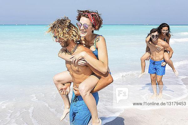 Freunde gehen am Strand spazieren und tragen Freundinnen huckepack