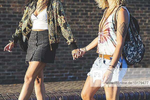 Zwei junge Frauen halten sich an den Händen und gehen an einer Ziegelmauer entlang