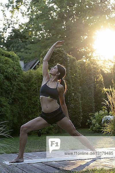 Frau praktiziert Yoga im Garten