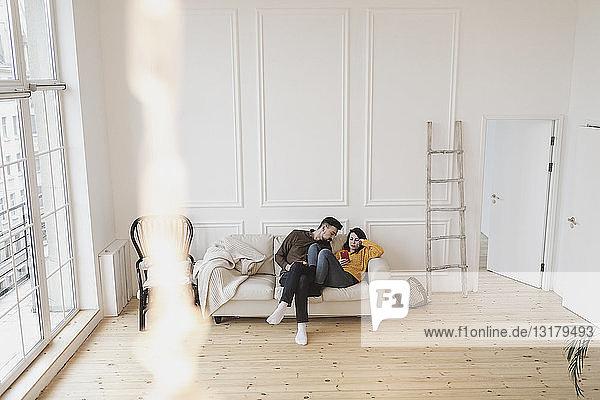Ehepaar sitzt auf der Couch im Wohnzimmer des neuen Zuhauses und schaut auf sein Handy
