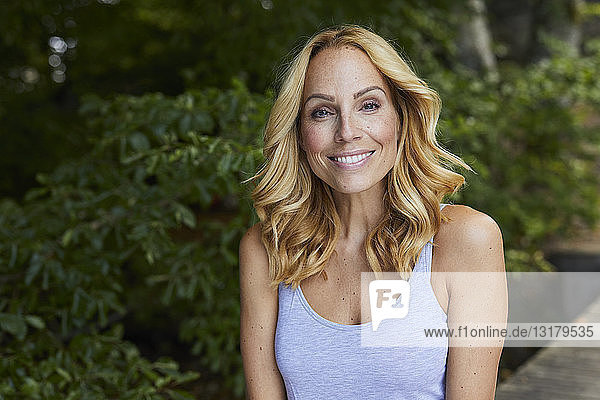 Porträt einer lächelnden blonden Frau im Freien