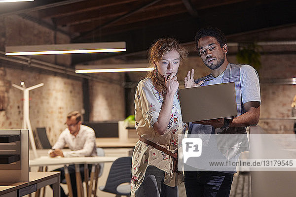 Man in office holding laptop  talking to colleague