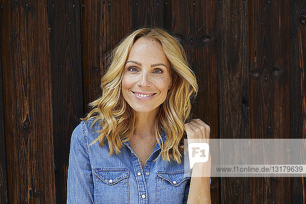 Portrait of smiling blond woman in front of wooden wall