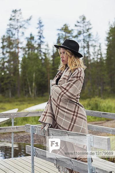 Finnland  Lappland  Frau mit einem Hut  der in eine Decke gehüllt ist  steht auf einem Steg am Seeufer