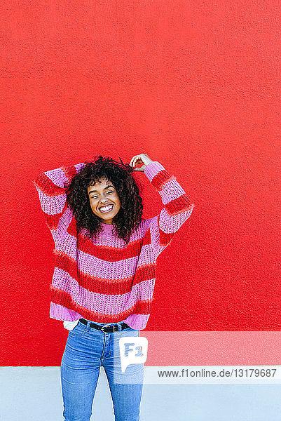 Porträt einer lachenden jungen Frau mit lockigem Haar vor roter Wand stehend