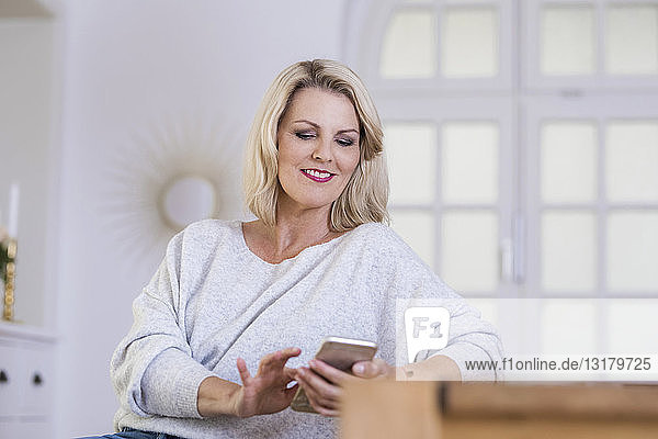 Portrait of smiling blond mature woman using smartphone at home