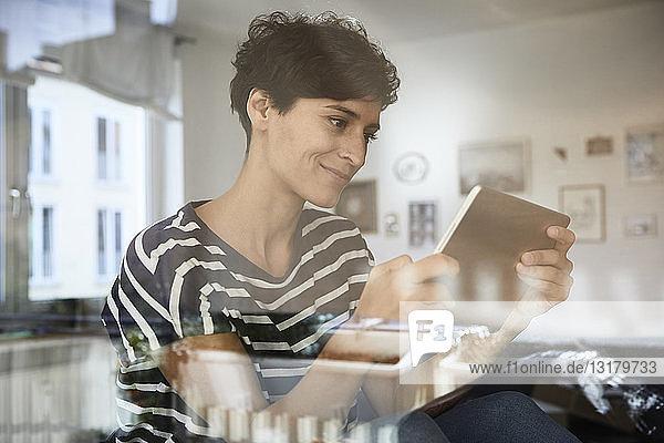 Frau benutzt Tablette zu Hause