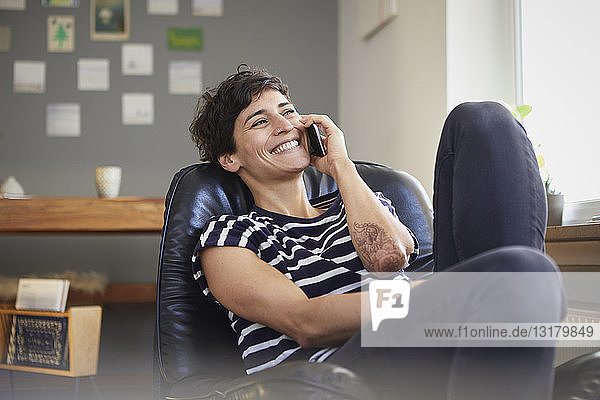 Happy woman talking on cell phone at home