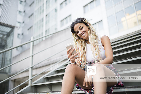 Young woman sitting on stairs  using smartphone