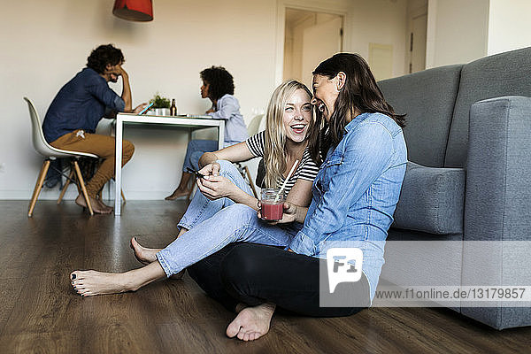 Two cheerful young women sitting on floor with cell phone and drink and friends in background