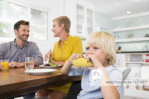 Junge isst Maiskolben in der Küche mit den Eltern im Hintergrund