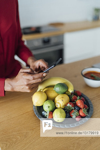 Woman taking pictures of fruits on a plate