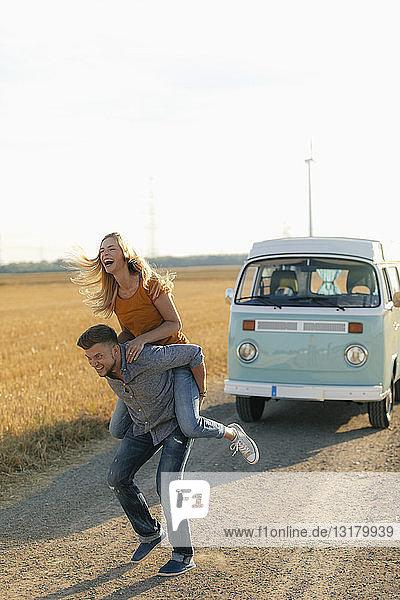 Verspieltes junges Paar im Wohnmobil in ländlicher Landschaft