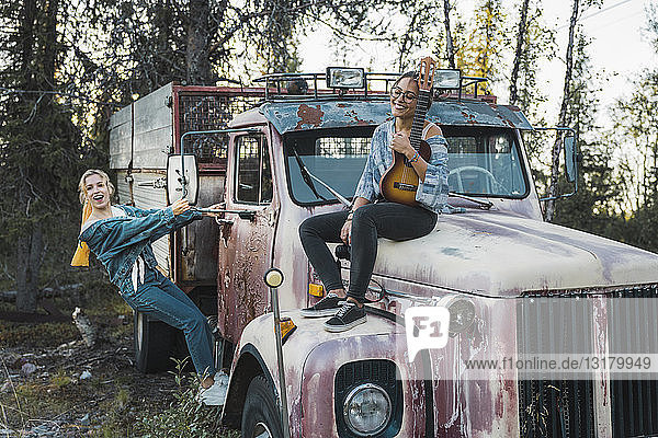 Two friends sitting on a broken truck  playing the ukulele
