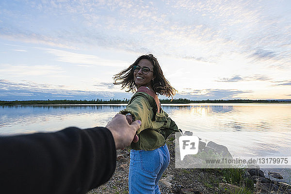 Finland  Lapland  happy young woman holding man's hand at the lakeside at twilight