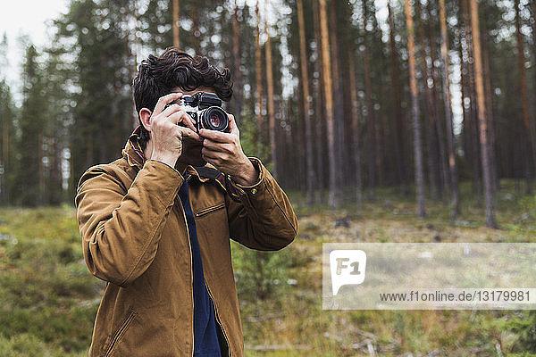 Finnland  Lappland  Mann beim Fotografieren in ländlicher Landschaft