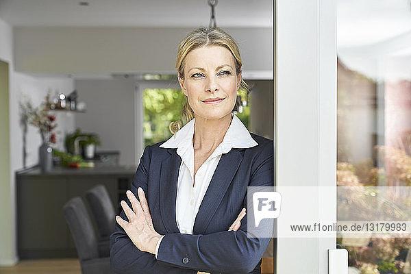 Porträt einer selbstbewussten Geschäftsfrau  die sich zu Hause an die französische Tür lehnt