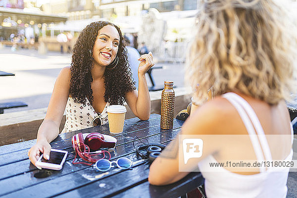 Two happy friends talking together at table outdoors